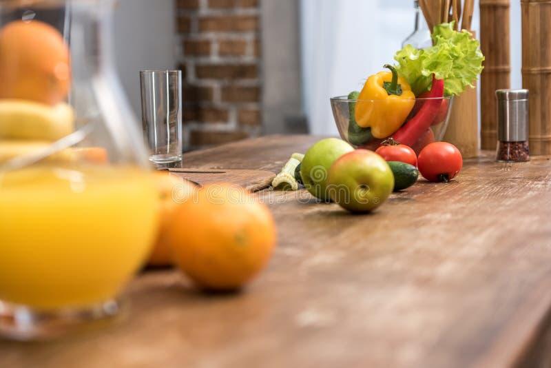 foco selectivo del zumo de naranja en el jarro de cristal, frutas y verduras frescas fotos de archivo libres de regalías