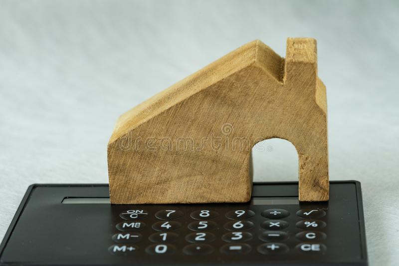 Foco selectivo en casa miniatura de madera en la calculadora negra como fotos de archivo