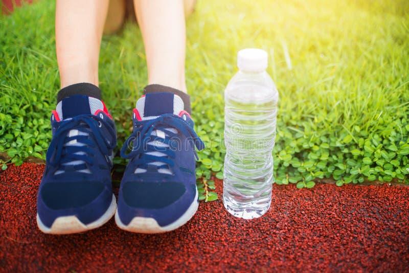 Foco selectivo en el chanclo, un comienzo gordo que corre para sano en hierba verde, ejercicio que activa de la mujer en el parqu foto de archivo libre de regalías