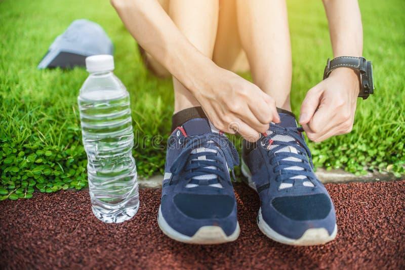 Foco selectivo en el chanclo, un comienzo gordo que corre para sano en hierba verde, ejercicio que activa de la mujer en el parqu fotografía de archivo libre de regalías