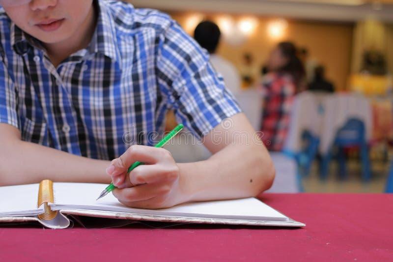 Foco selectivo en las manos de la escritura joven del hombre de la huésped en el libro de la memoria para bendecir palabra para p fotos de archivo