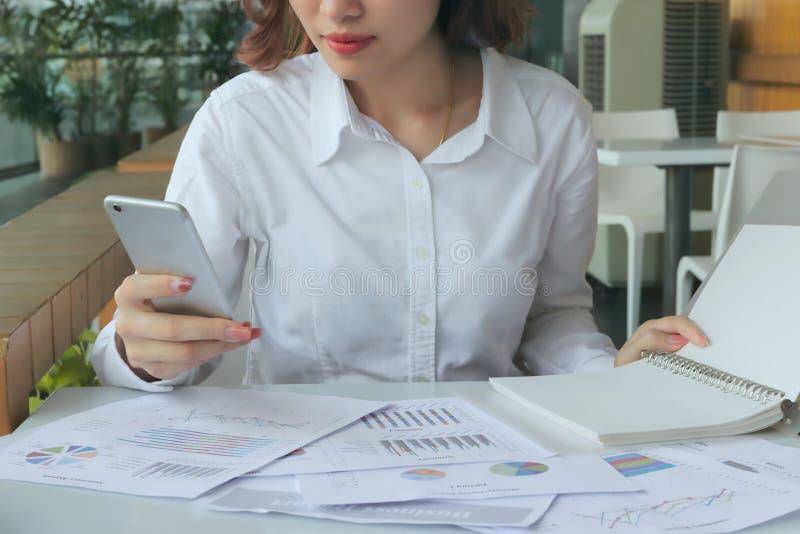Foco selectivo en las manos de la mujer de negocios que sostienen el teléfono elegante móvil con las cartas o el papeleo en lugar foto de archivo libre de regalías
