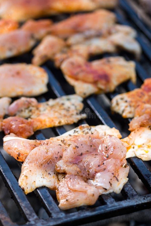 Foco selectivo en las pechugas de pollo que fríen en la parrilla de la barbacoa imagen de archivo