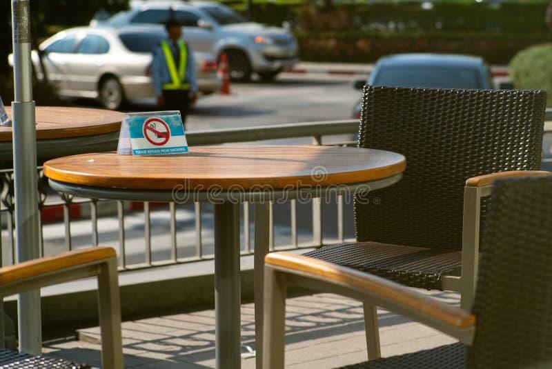 Foco selectivo en muestra no fumadora en las sillas de madera de la tabla y de la vacante del vintage en la terraza de la cafeter fotos de archivo libres de regalías