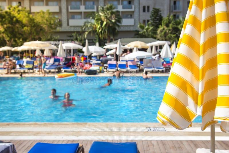 Foco selectivo en piscina en centro turístico tropical en el paraguas claro del día soleado y de sol en foco Báñese en piscina en foto de archivo libre de regalías