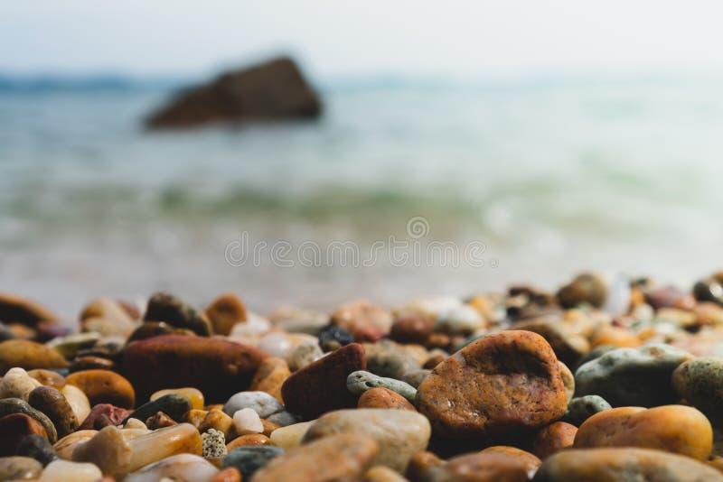 Foco selectivo en textura de las rocas con la playa de la falta de definición foto de archivo
