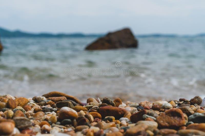 Foco selectivo en textura de las rocas con la playa de la falta de definición imagenes de archivo