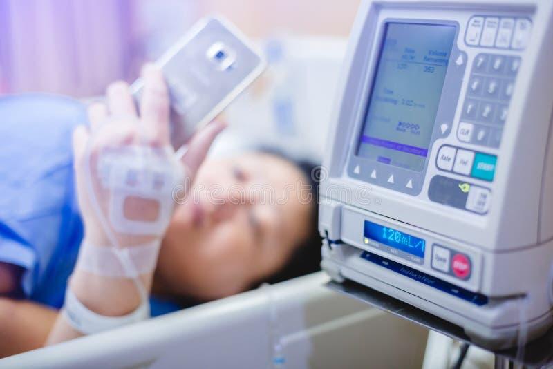 Foco selectivo a las bombas de la infusión con el teléfono elegante del juego paciente borroso en hospital foto de archivo libre de regalías