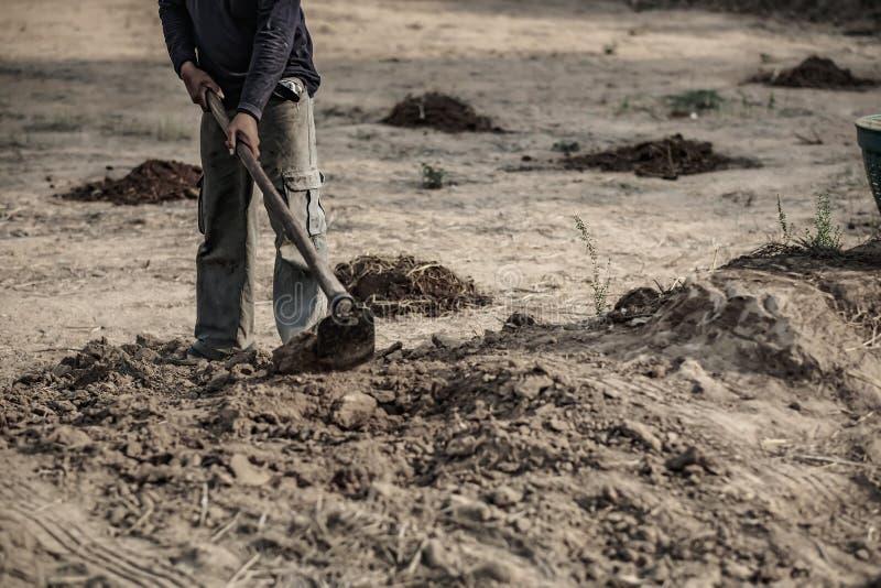 Foco selectivo, suelo del empuje del granjero al trabajo fotografía de archivo libre de regalías