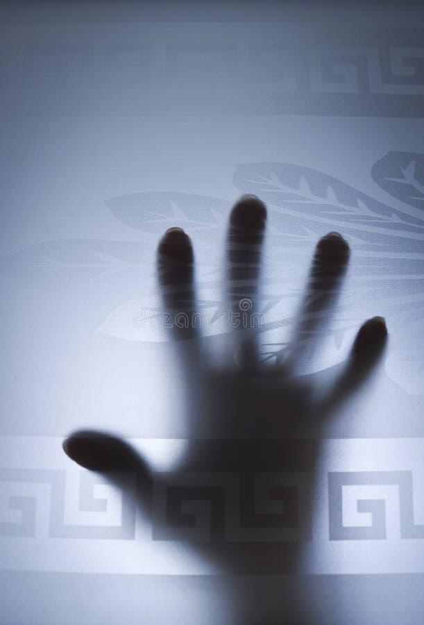 Foco seletivo - as mãos mostram em silhueta atrás de uma porta de vidro geada O conceito do medo, perigo imagem de stock royalty free