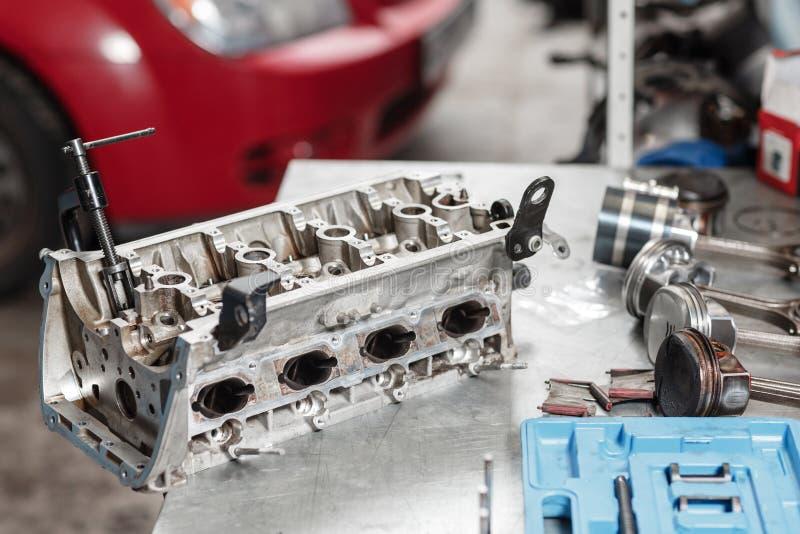 Foco seletivo Bloco de motor em um suporte do reparo com pistão e conexão Rod da tecnologia automotivo Carro vermelho borrado imagem de stock royalty free
