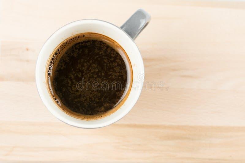 Foco seletivo da configuração lisa acima da xícara de café na placa de madeira borrada com espaço vazio da cópia imagens de stock