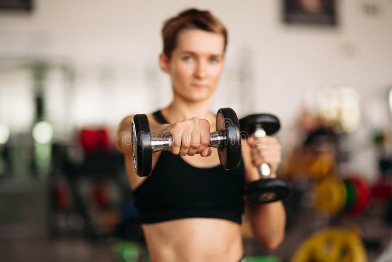 Foco seletivo da mulher desportiva com pesos do peso no gym imagens de stock