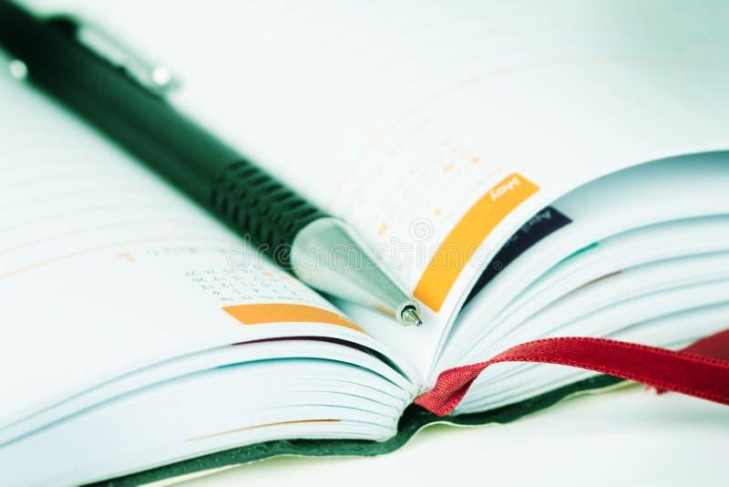 Foco seletivo da pena de bola no livro alinhado aberto do diário com cale foto de stock