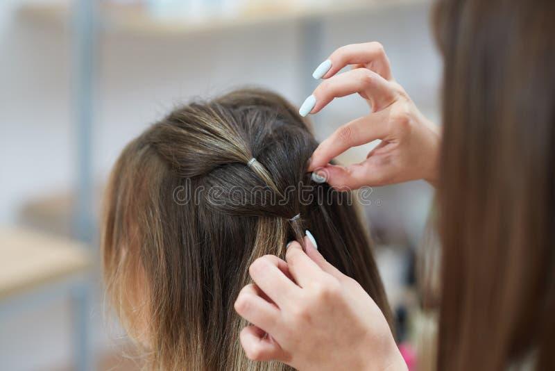 Foco seletivo das mãos do spikelet da trança do cabeleireiro ao cliente no salão de beleza imagens de stock
