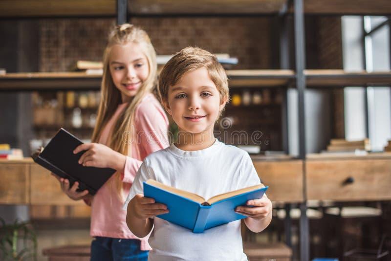 foco seletivo de irmãos de sorriso com livros fotografia de stock