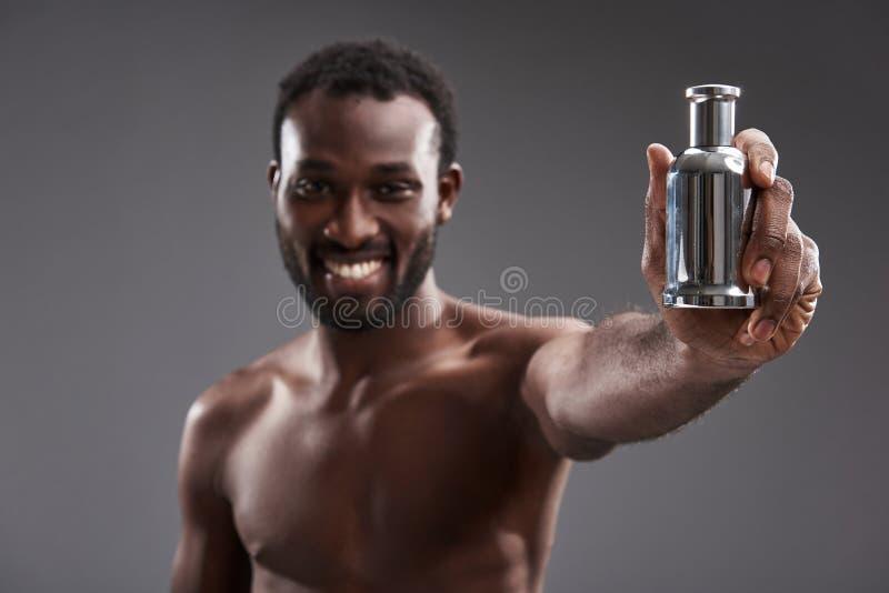 Foco seletivo de um perfume nas mãos de um homem afro-americano alegre foto de stock royalty free