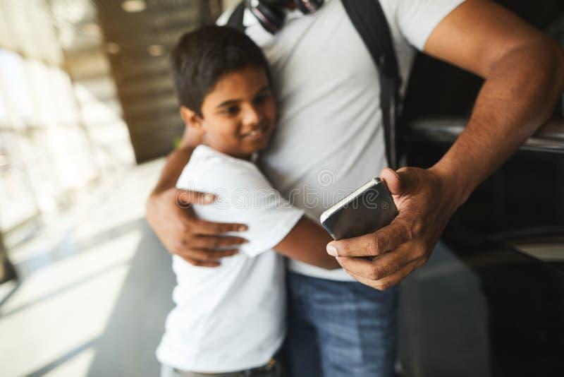 Foco seletivo de um smartphone nas mãos de um pai hindu de inquietação fotografia de stock