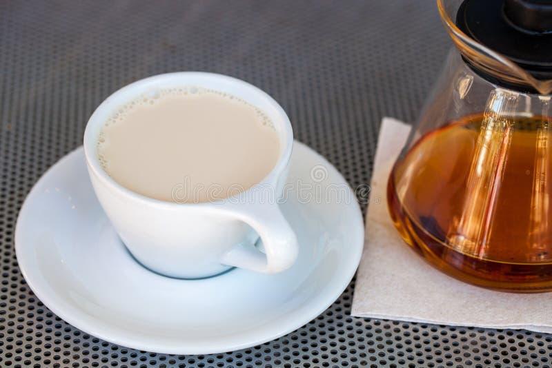 Foco seletivo do chá preto com leite no copo branco da porcelana com o bule ao lado dele em uma tabela metálica imagens de stock