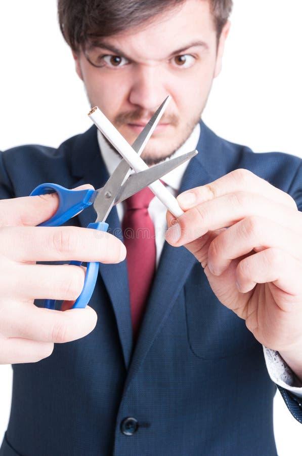 Foco seletivo do homem louco que corta um cigarro imagem de stock royalty free