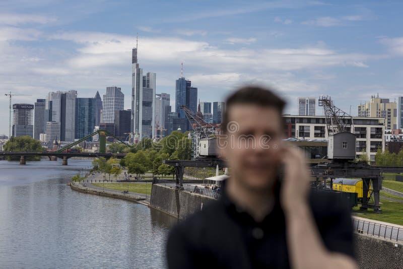 Foco seletivo do homem que fala na skyline do telefone celular e da cidade fotos de stock royalty free
