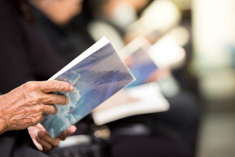 Foco seletivo do livro de oração da terra arrendada do ancião na igreja fotos de stock royalty free