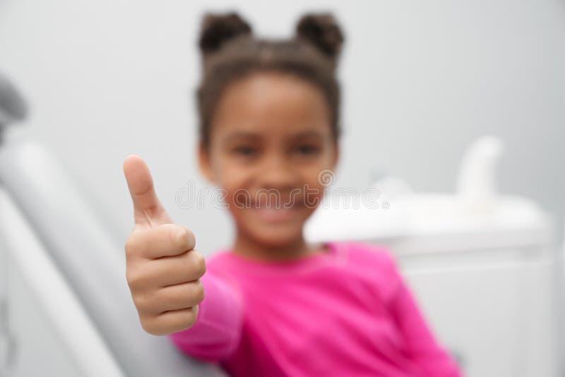 Foco seletivo do polegar acima da menina no escritório do dentista fotografia de stock