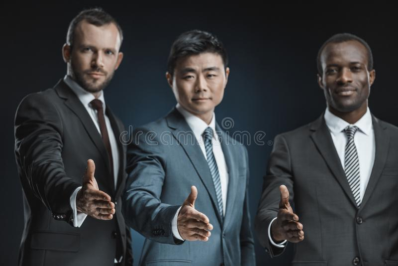 foco seletivo dos executivos multi-étnicos que outstretching as mãos para o aperto de mão fotografia de stock