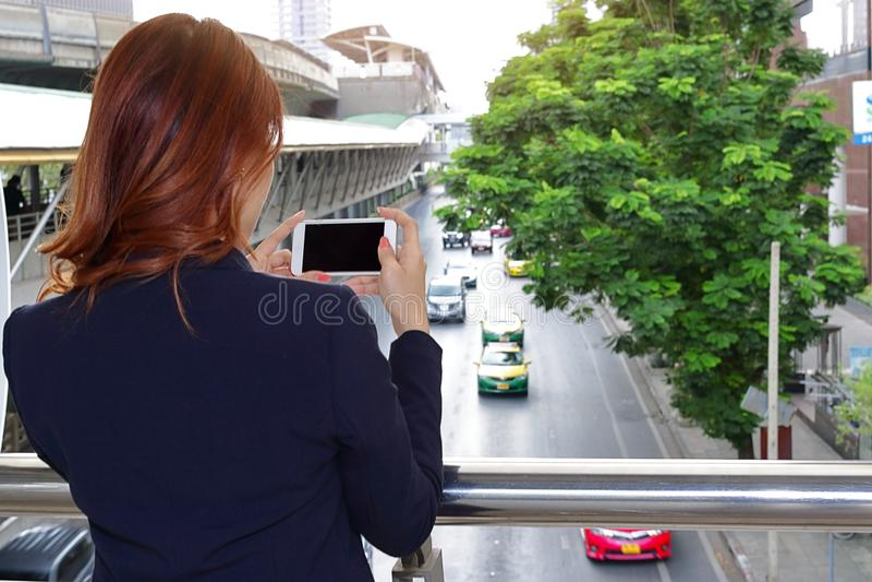 Foco seletivo e profundidade de campo rasa Opinião traseira a mulher que toma uma foto do carro do tráfego na cidade com o telefo imagens de stock