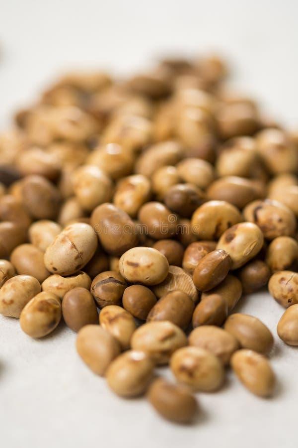 Foco seletivo em grãos de soja na tabela de mármore branca do fundo foto de stock