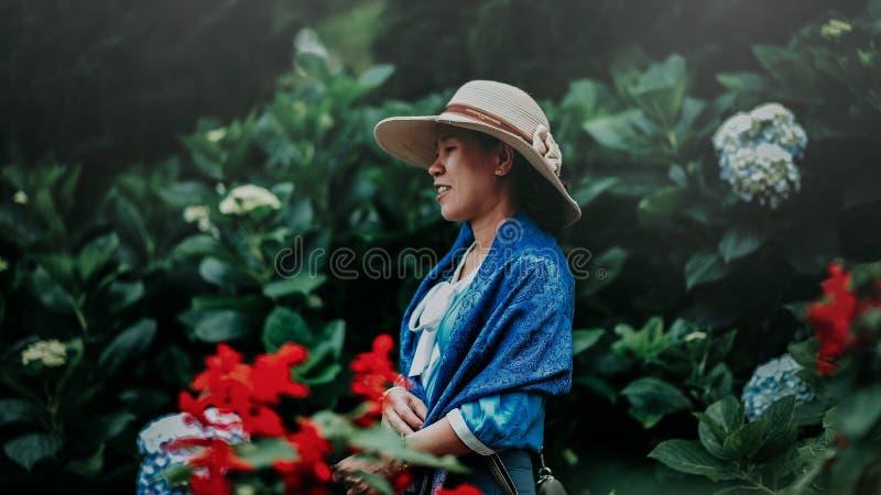 Foco seletivo Foto de Mulher em Blue Shawl e Brown Sun Hat no meio do jardim foto de stock royalty free