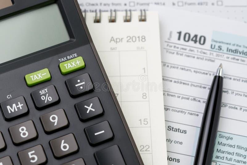 Foco seletivo na calculadora na pena do calendário e no formulário do imposto de renda de 1040 E.U., na submissão do imposto ou n foto de stock