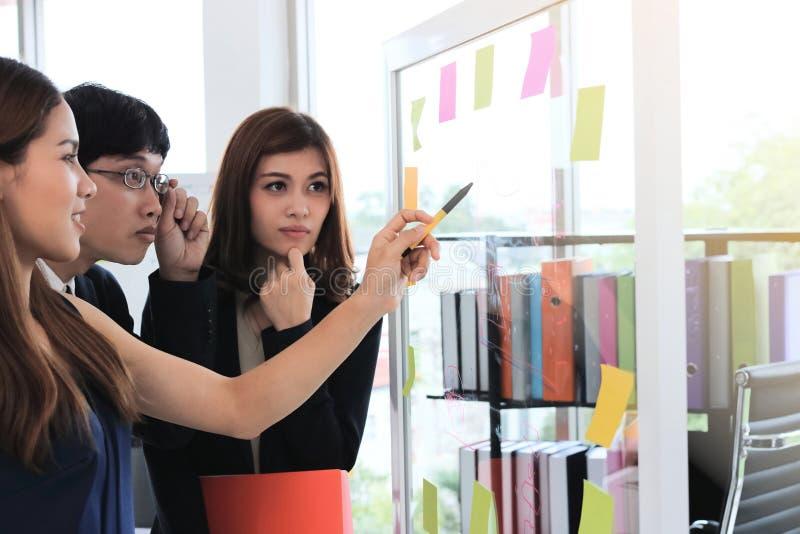 Foco seletivo nas mãos dos executivos asiáticos novos que explicam estratégias na aleta na sala de conferências imagem de stock