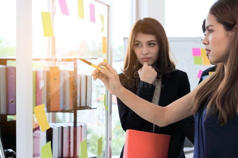 Foco seletivo nas mãos dos executivos asiáticos novos que explicam estratégias na aleta na sala de conferências com efeito da luz imagem de stock