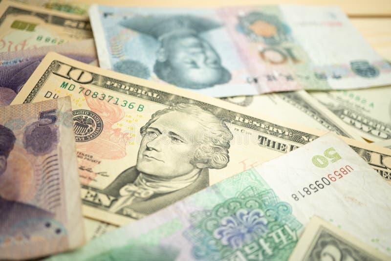 Foco seleto da pilha do dólar americano 10 sob a cédula do yuan de China Conceito da guerra comercial entre o Estados Unidos e a  foto de stock royalty free