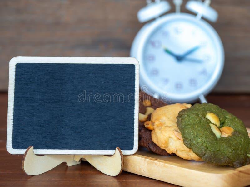 Foco seleto do quadro-negro na frente da manteiga de amendoim inclusiva das cookies múltiplas da cor, das cookies do chá verde, e fotos de stock