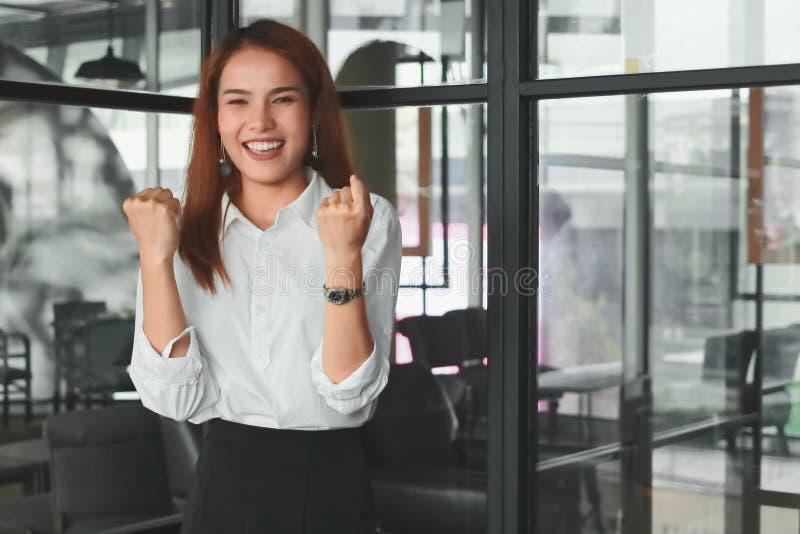 Foco suave de la empresaria asiática joven sonriente que aumenta las manos en oficina Concepto acertado de la mujer de negocios fotos de archivo
