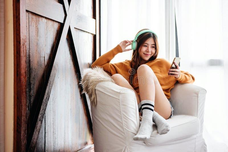 Foco suave de la mujer joven feliz que se relaja por el auricular de la música de Smartphone en el sofá en casa acogedora foto de archivo