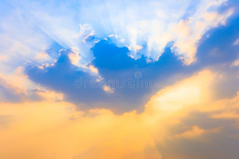 Foco suave en la nube y el rayo de sol de la luz del sol o rayo solar a través del cielo azul en la puesta del sol o el tiempo de fotos de archivo