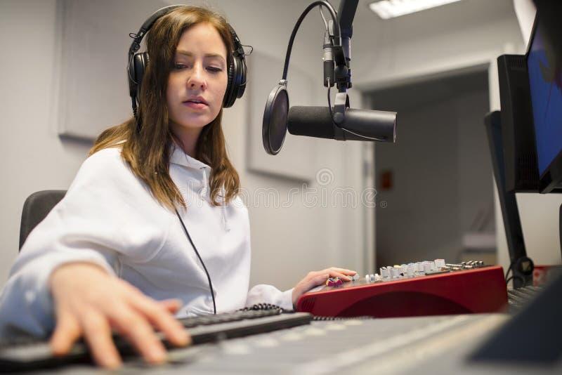 Focsued收音机主人佩带的耳机在演播室 免版税图库摄影