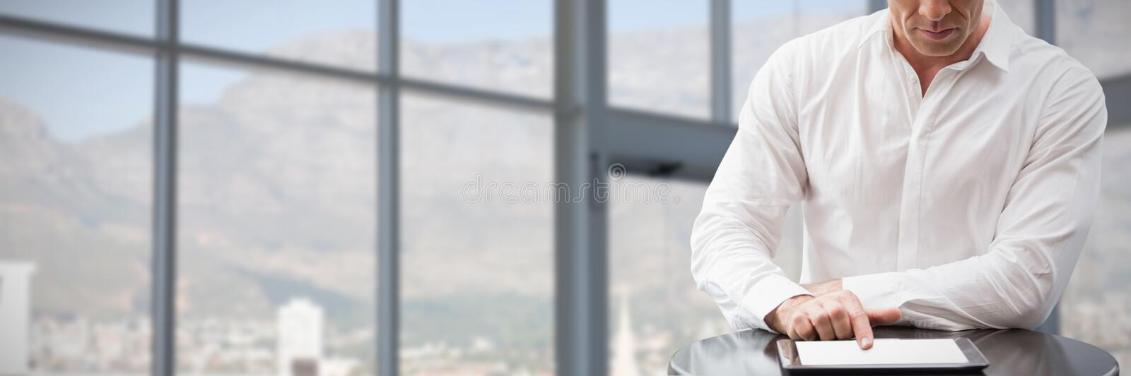 Composite image of focues businessman using digital tablet while sitting against white background. Focues businessman using digital tablet while sitting against stock image