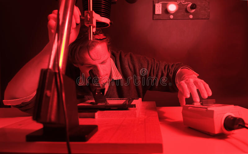 Focus. Photographer working in a darkroom, printing analogue negatives with an enlarger, fine-tuning the focus of the image on the easel with a scope, hands on stock images