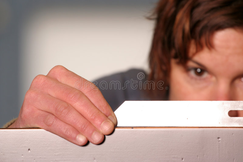 Focus. A woodworker checks her work with a square. Shallow depth of field, focus on her hands royalty free stock images