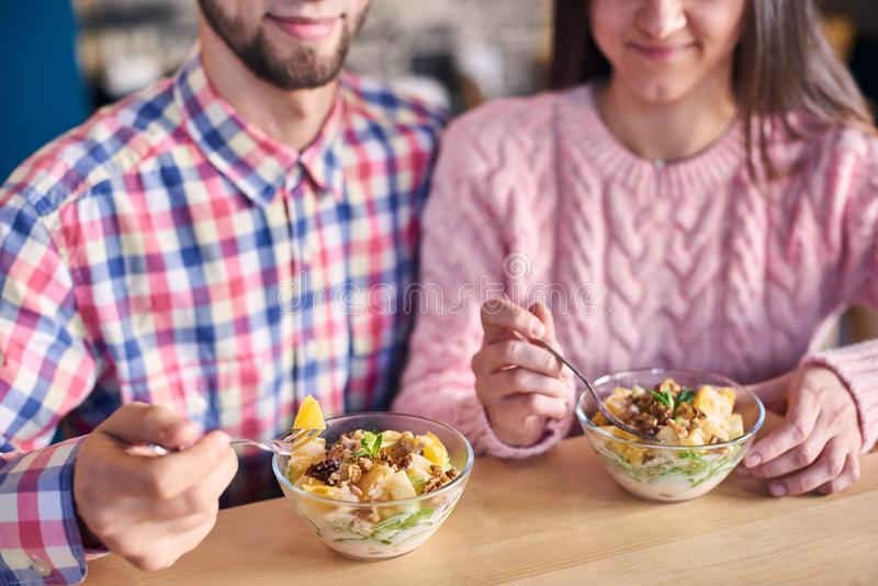 Focus on bowl with dessert useful light fruit salad. Concept of family healthy lifestyle and diet. Blurred background. royalty free stock photo