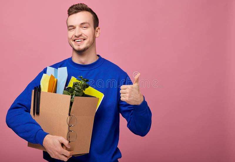 Pretty guy is hugging box with green plant, yelow notebook and paper airplane and show like stock photo
