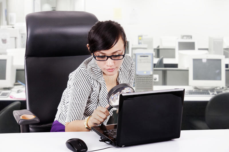 Focus business woman using magnifying glass. Business woman with magnifying glasses and laptop at office royalty free stock photo
