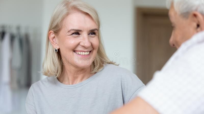 Focus on caregiver face female assisting patient listening older man. Close up focus on smiling 50s or 60s women communicates with old man, adult daughter and royalty free stock images