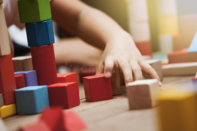 Focus on child`s hand playing with colorful wooden blocks royalty free stock images