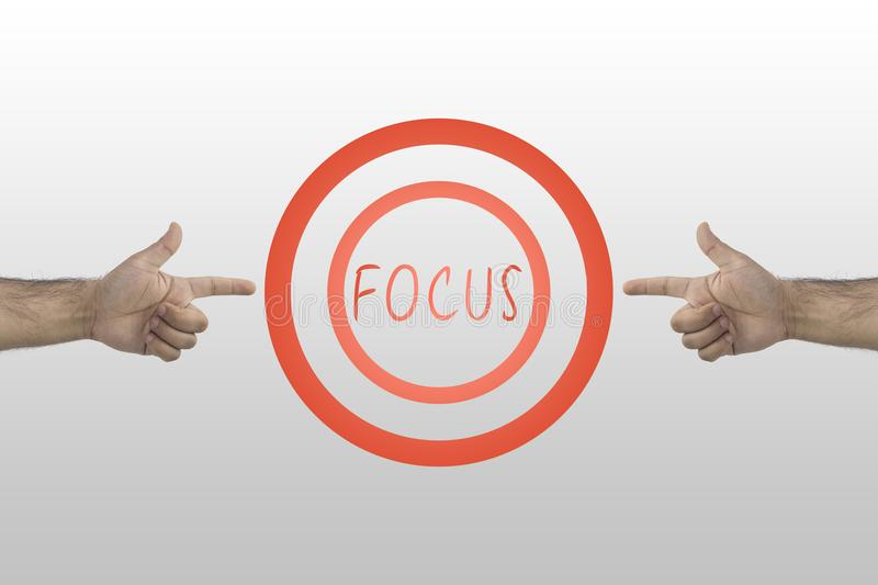 Focus concept. Business concept. Two hands pointing to drawn aim with text in the center: Focus stock image