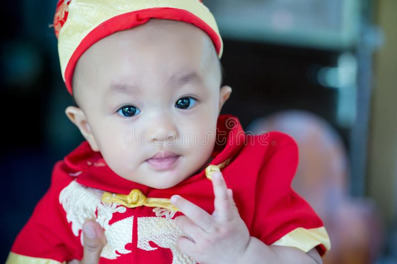 Focus cute baby boy wear red and gold chinese suit on chinese new year day. Fancy clothes for baby and child. pretty infant. Asian baby boy.image for stock images
